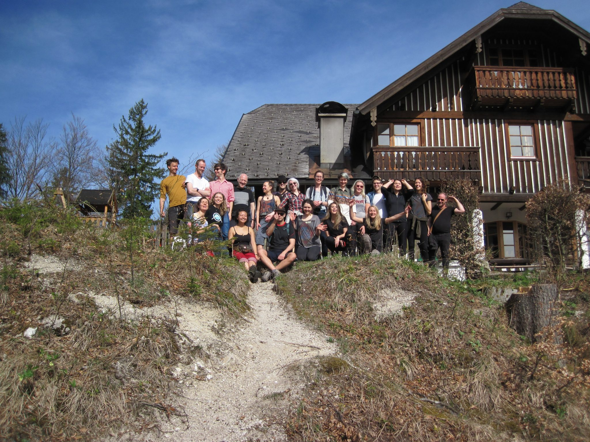 group of people standing outside a mountain lodge