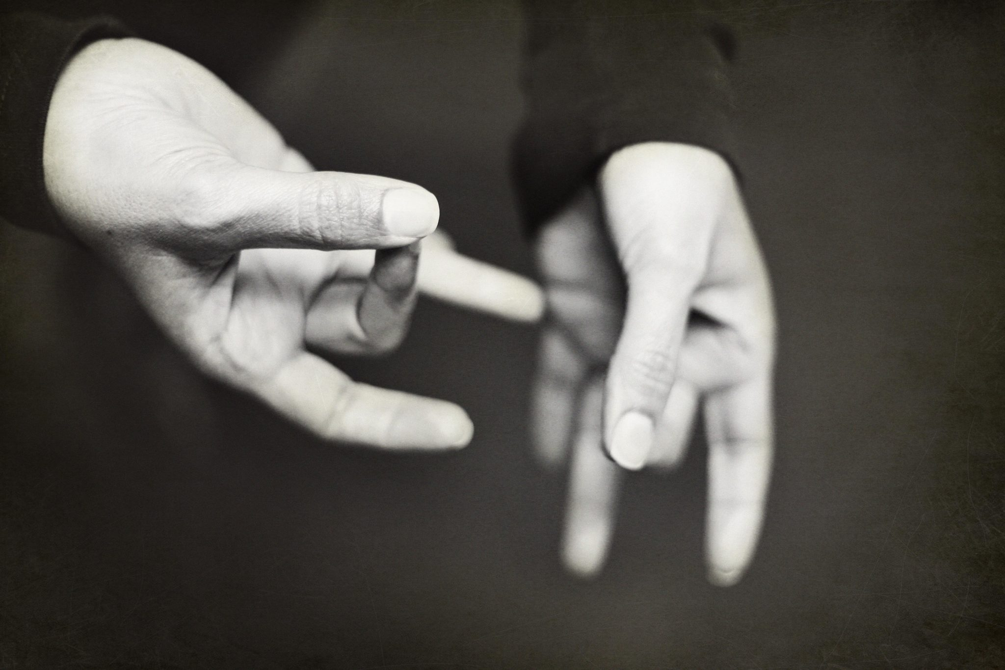 Black and white photo of hands signing