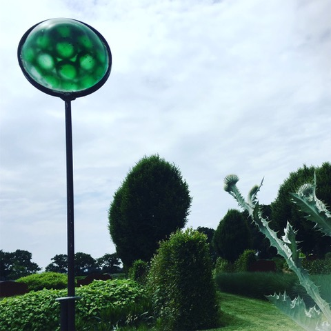 Green glass sculpture on a metal rod sticking up into the air in a garden.