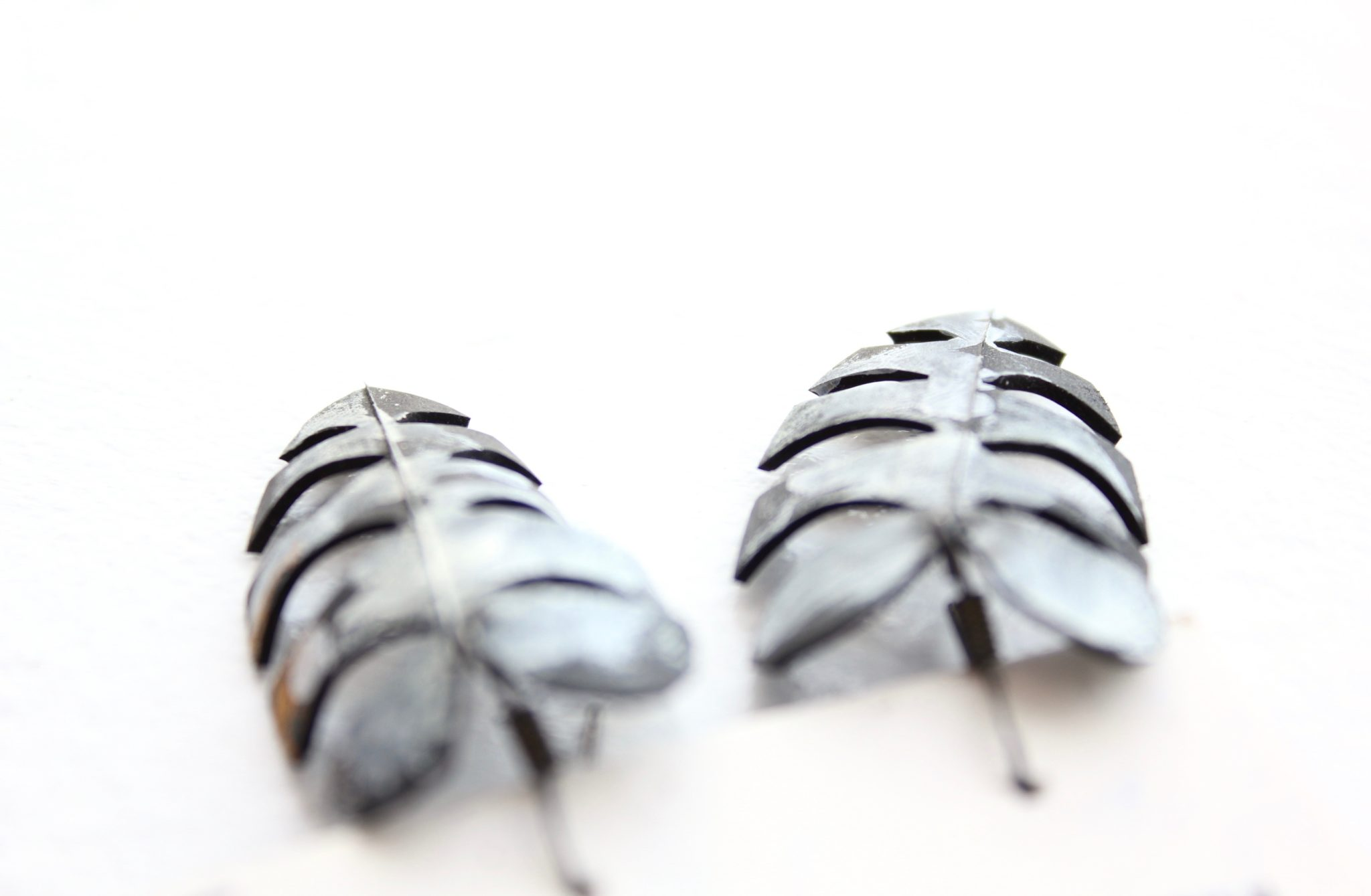 Detail of fern-shaped upcycled bike tube earrings by Tubed Jewellery