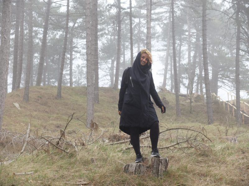 photo of smiling person standing in misty woodland