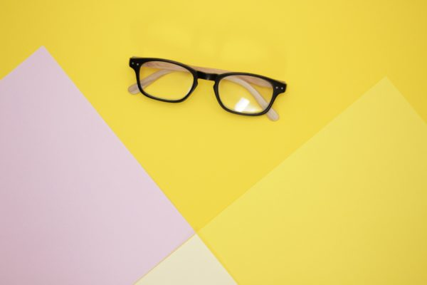 black glasses on yellow and pink background