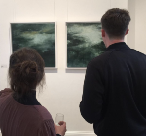 two people looking at paintings on wall