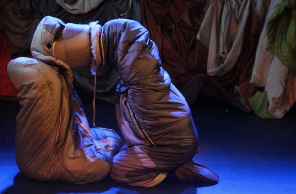 two performers onstage inside sleeping bags