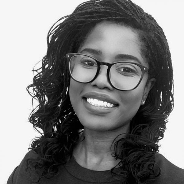 Black and white headshot of black woman with curly hair and glasses, smiling.