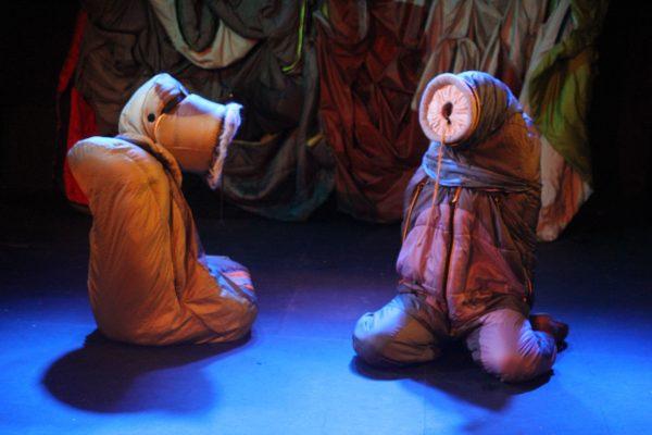 Two people dressed in sleeping bags and kneeling on the floor